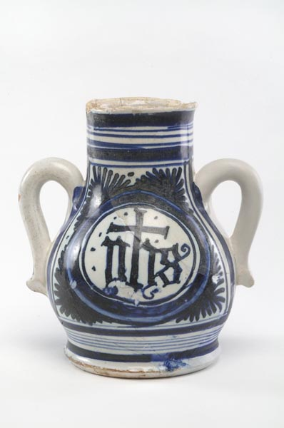 White vase with 2 handles. It is decorated in blue with bands around the neck and base and with the initials 'YHS' in the centre of the body.