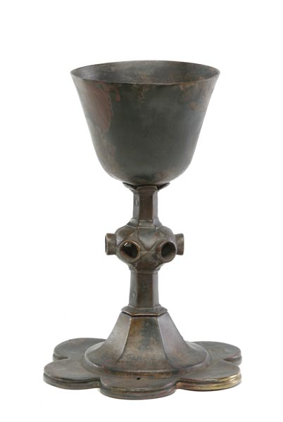 Brass chalice with a hexagonal stem. In the middle of the stem are empty holes where precious stones used to be set. The base is shaped like the petals of a flower.