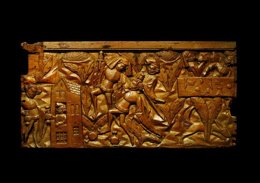 Carved wooden panel depicting Chaucer's Pardoner's Tale. On the left a man buys wine from an inn. In the centre the man is stabbed by 2 other men. On the right the 2 men sit at a table and drink wine.