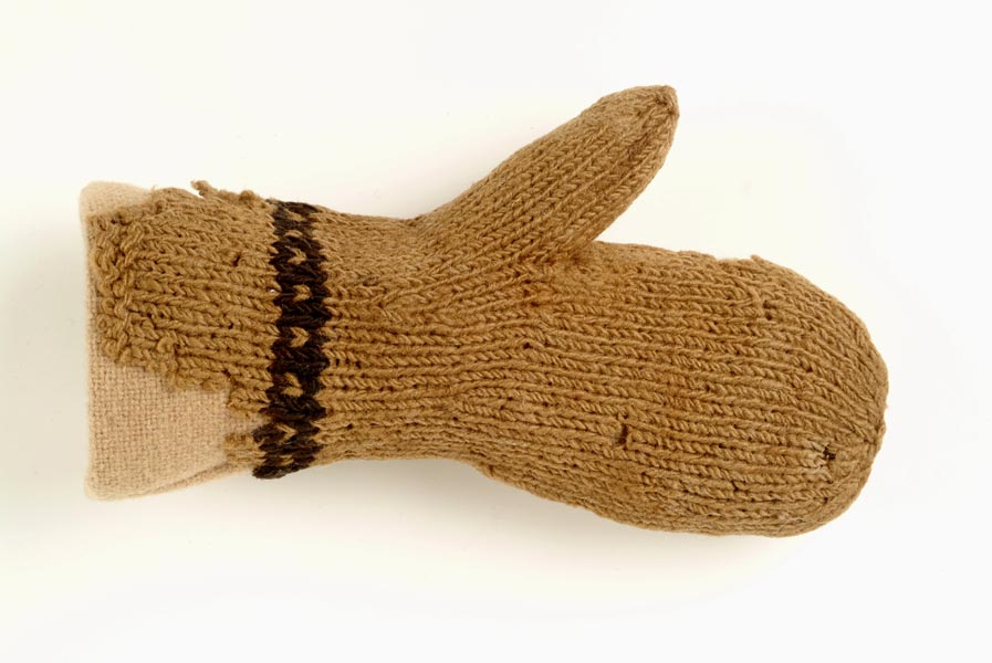 Small knitted woollen mitten. The wool is pale brown. There is a line of black wool decoration around the wrist.