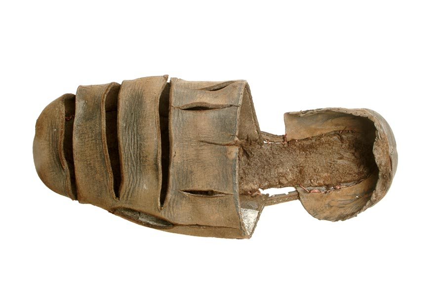 Brown leather shoe with 3 large slashes across the front and smaller slashes around the opening for the foot.