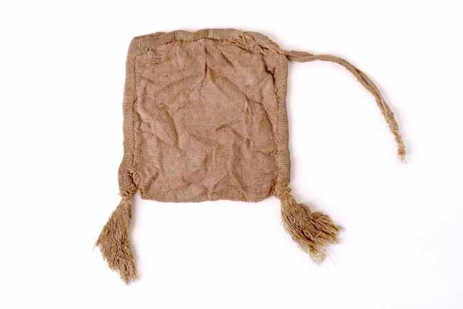 Small square. Flat silk purse with 2 tassels at the bottom and a drawstring at the top. The silk has faded to a beige colour.