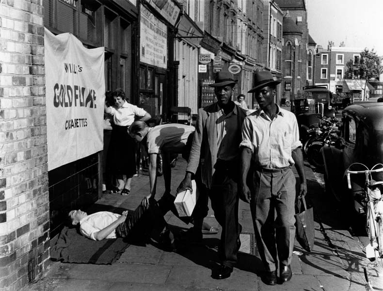 Two Black men wearing hats walk down a street lined with shops and cars.