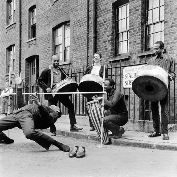 Three men play steel drums, one man plays a drum and another limbo dances barefoot beneath a low bar.