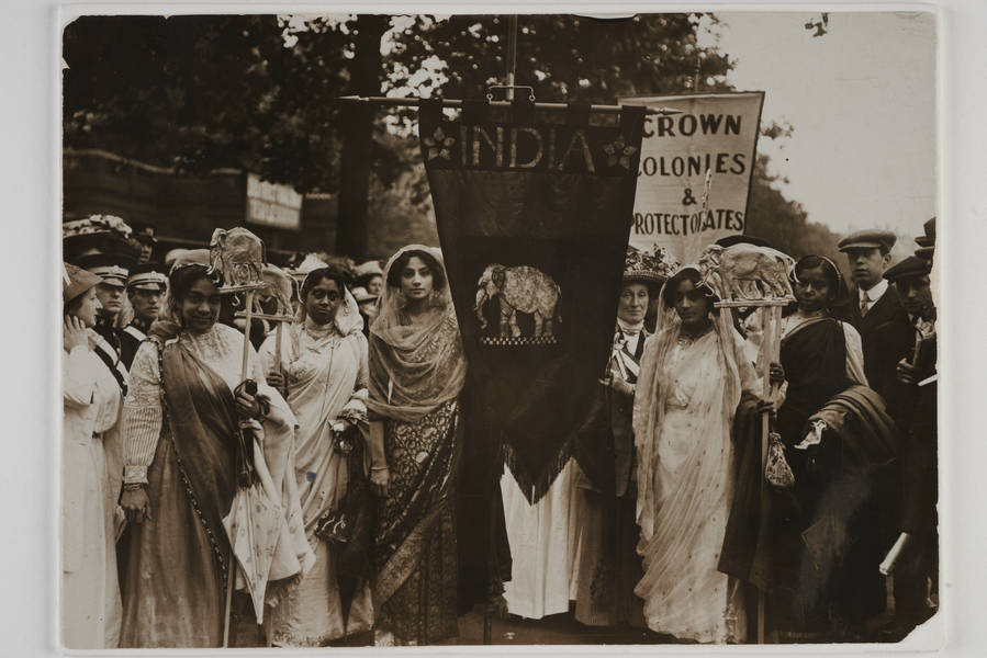 Group of Indian women dressed in saris, carrying staffs topped with elephants and banners.